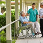 Two senior citizens talking to a nurse in a hospital garden